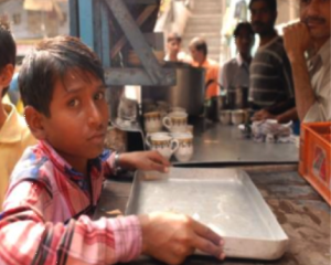 A boy holds an empty tray for food.