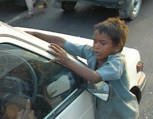 Small boy tries to clean a windshield.