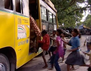 Children run to climb on the learning bus