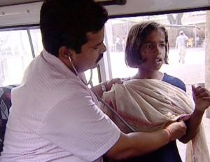 A doctor on a van listens to the heart of a young girl.