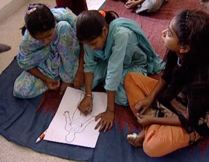 3 girls work together over the drawing of a human figure.