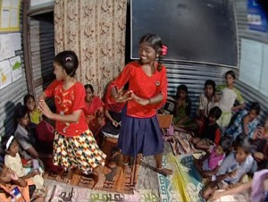 Two young girls dancing for students.