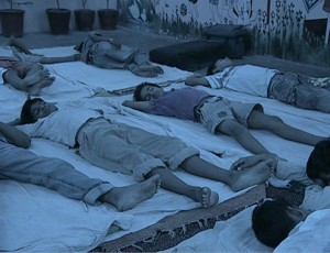 A group of boys sleep peacefully on mats.